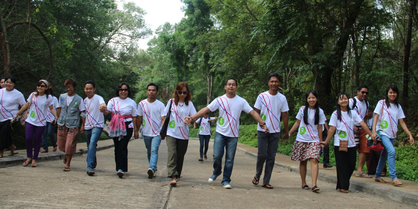 Oxfam in Myanmar staff are holding hands in hands together, working towards the world without poverty and injustice. Photo by: Yee Mon Oo/ Oxfam