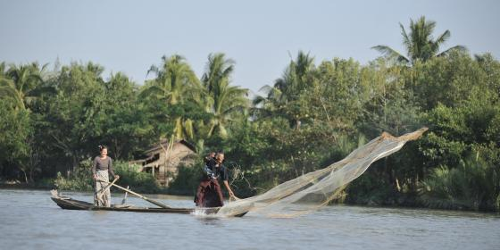 Man fisher folk is throwing the fishing net into the river and his wife is rowing the boat in Ayeyarwaddy region. Photo by: Kaung Htet/ Oxfam